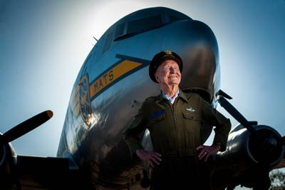 """Retired Col. Gail S. Halvorsen, known commonly as the Berlin """"Candy Bomber,"""" stands in front of a C-54 Skymaster like the one he flew during WWII at the Pima Air and Space Museum in Arizona. Halvorsen dropped candy bars attached to parachutes made from handkerchiefs to German children watching the airlift operations from outside the fence of the Tempelhof Airport in West Berlin. (U.S. Air Force photo/Bennie J. Davis III)"""