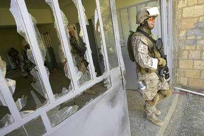 This file photo from Aug. 6, 2005, shows U.S. Marine Staff Sgt. Brian Hamilton of Columbus, Ohio, from Lima Company of the 3rd Battalion, 25th Regiment as he exits after searching a school, in Parwana, near Haditha, Iraq.