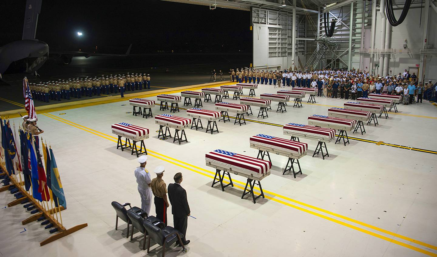 """In this Wednesday, July 17, 2019 photo, service members and guests stand as """"Taps"""" is played over transfer cases carrying the possible remains of unidentified service members lost in the Battle of Tarawa during World War II in a hangar at Joint Base Pearl Harbor-Hickam in Hawaii."""