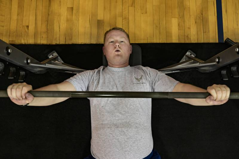Senior Airman James Fritz, 911th Airlift Wing public affairs specialist, performs a barbell bench press in the gym at the Pittsburgh International Airport Air Reserve Station, Pennsylvania, Jan. 25, 2021. Although all Air Force fitness tests are suspended until July, all Airmen are expected to maintain their personal physical readiness. (Joshua J. Seybert/Air Force)