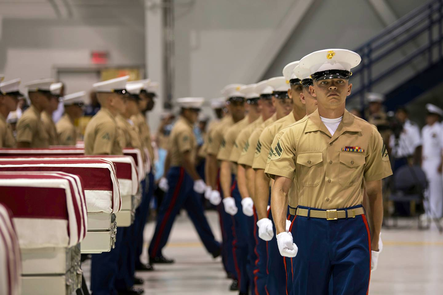 In this Wednesday, July 17, 2019 photo, Marines march past transfer cases carrying the possible remains of unidentified service members lost in the Battle of Tarawa during World War II in a hangar at Joint Base Pearl Harbor-Hickam in Hawaii.