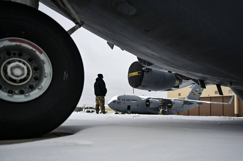 An Airman assigned to the 911th Aircraft Maintenance Squadron conducts a walk-around inspection on a C-17 Globemaster III at the Pittsburgh International Airport Air Reserve Station, Pennsylvania, on Feb. 1, 2021. (Joshua J. Seybert/Air Force)