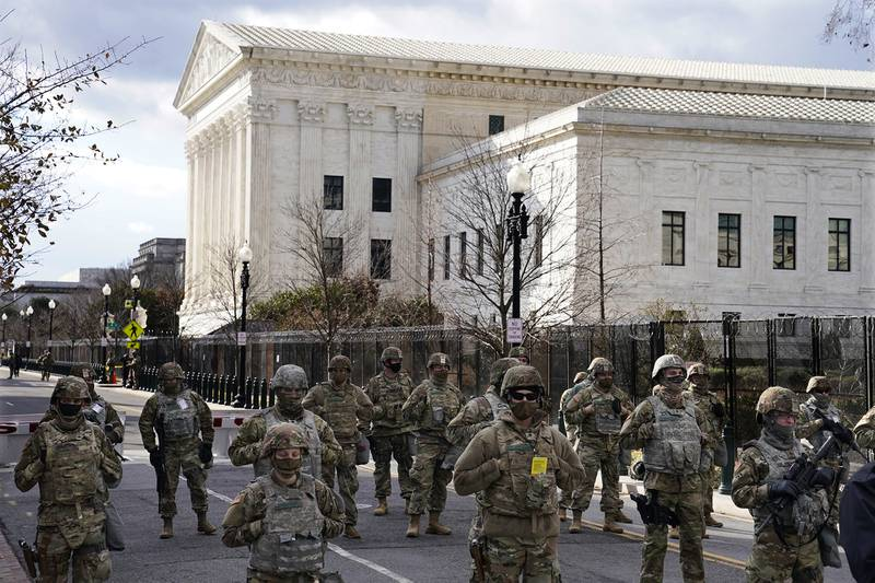 Members of the National Guard stand at a road block near the Supreme Court ahead of President-elect Joe Biden's inauguration ceremony, Wednesday, Jan. 20, 2021, in Washington.