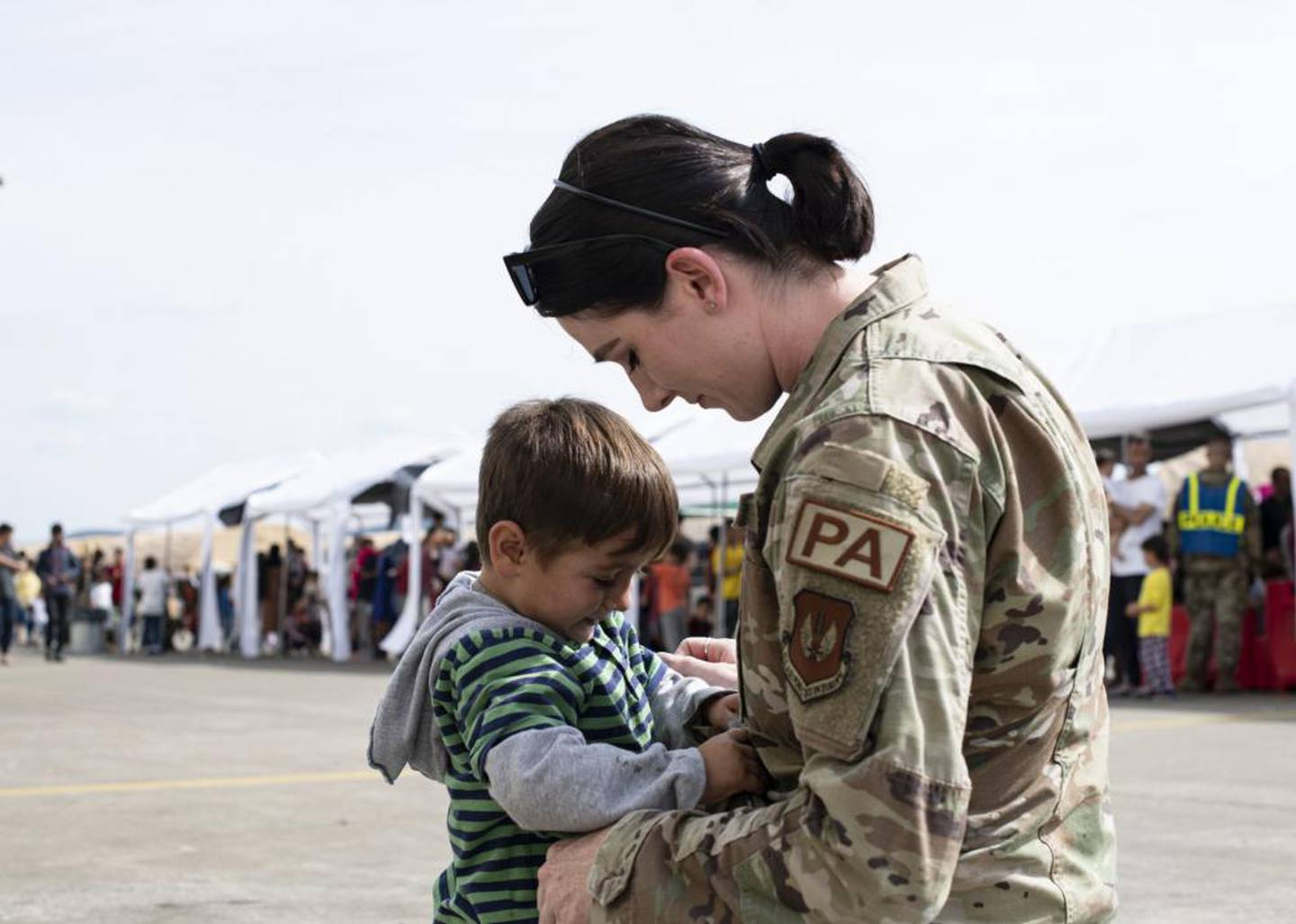 U.S. Air Force Capt. Shelby Chapman, 86th Airlift Wing Public Affairs Mission Partner Support chief, comforts a child at Ramstein Air Base, Germany, Sept. 7, 2021. Chapman leads the community engagement team for Operation Allies Refuge. (Staff Sgt. Jourdan Barrons/Air Force)