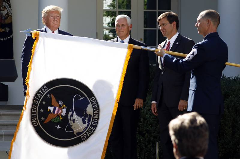 In this Aug. 29, 2019, file photo, President Donald Trump watches with Vice President Mike Pence and then-Defense Secretary Mark Esper as the flag for U.S. Space Command is unfurled as Trump announces the establishment of the U.S. Space Command in the Rose Garden of the White House in Washington.