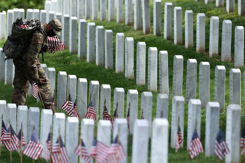 """Wearing face masks to reduce the risk of spreading the novel coronavirus, soldiers from the 3rd Infantry Regiment, also called the """"Old Guard,"""" place U.S. flags in front of every grave site ahead of the Memorial Day weekend in Arlington National Cemetery on May 21, 2020, in Arlington, Va."""