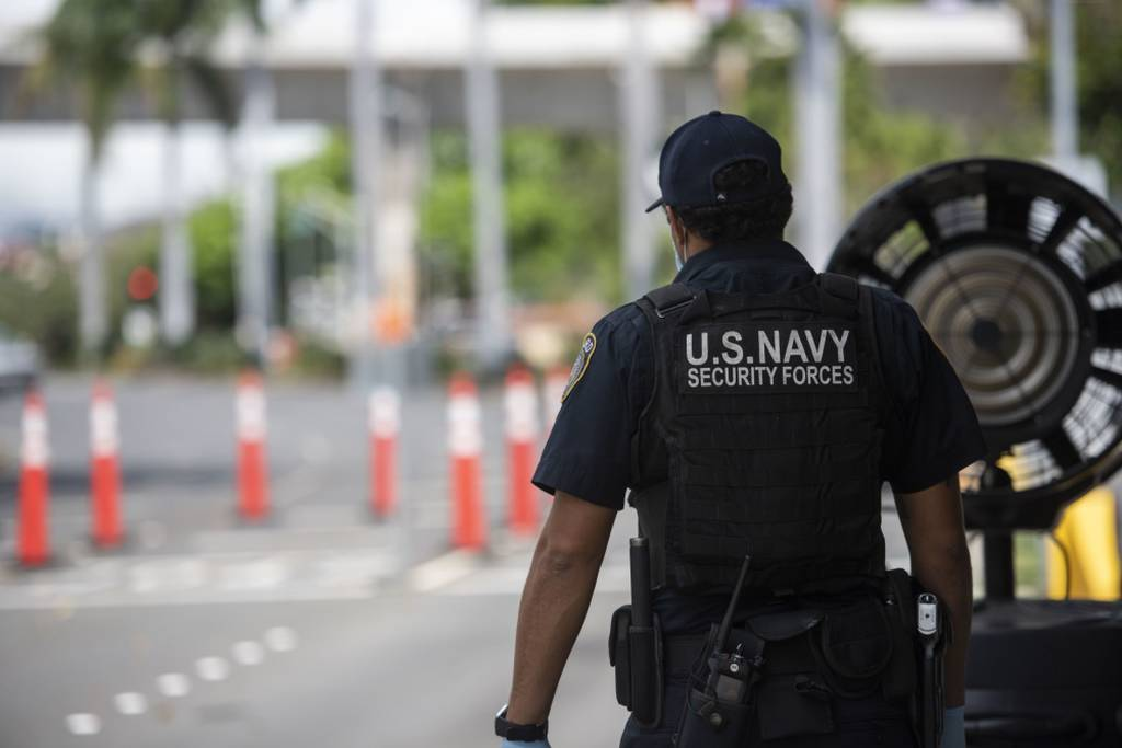 Guard Officer Luis Abreu, a Navy police officer, stands post at the Makalapa gate at Joint Base Pearl Harbor-Hickam, Hawaii, April 13, 2020. (Specialist 2nd Class Charles Oki/U.S. Navy)