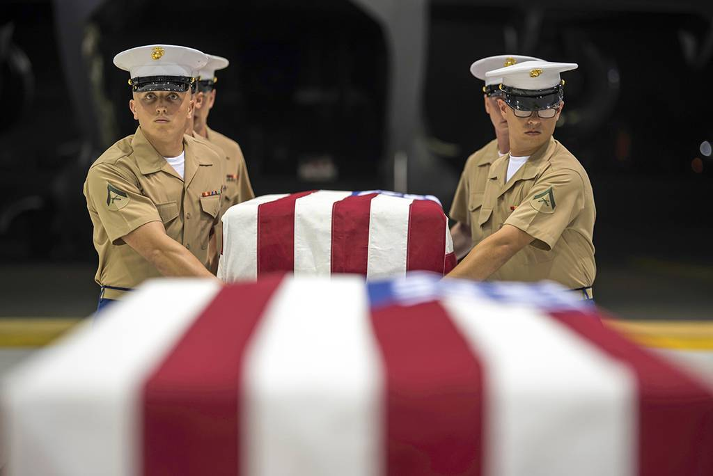 In this Wednesday, July 17, 2019, photo, Marines carry transfer cases holding the possible remains of unidentified service members lost in the Battle of Tarawa during World War II in a hangar at Joint Base Pearl Harbor-Hickam in Hawaii.