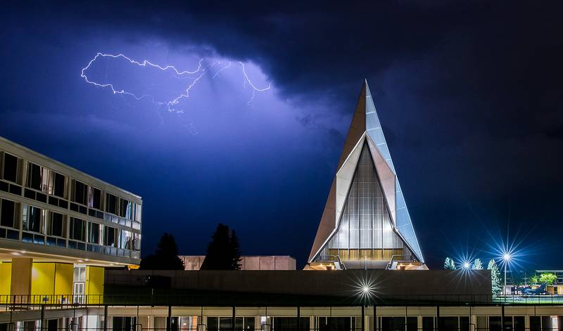 A late evening thunderstorm on Aug. 2, 2019, lights up the sky above the Cadet Chapel at the U.S. Air Force Academy, Colo.