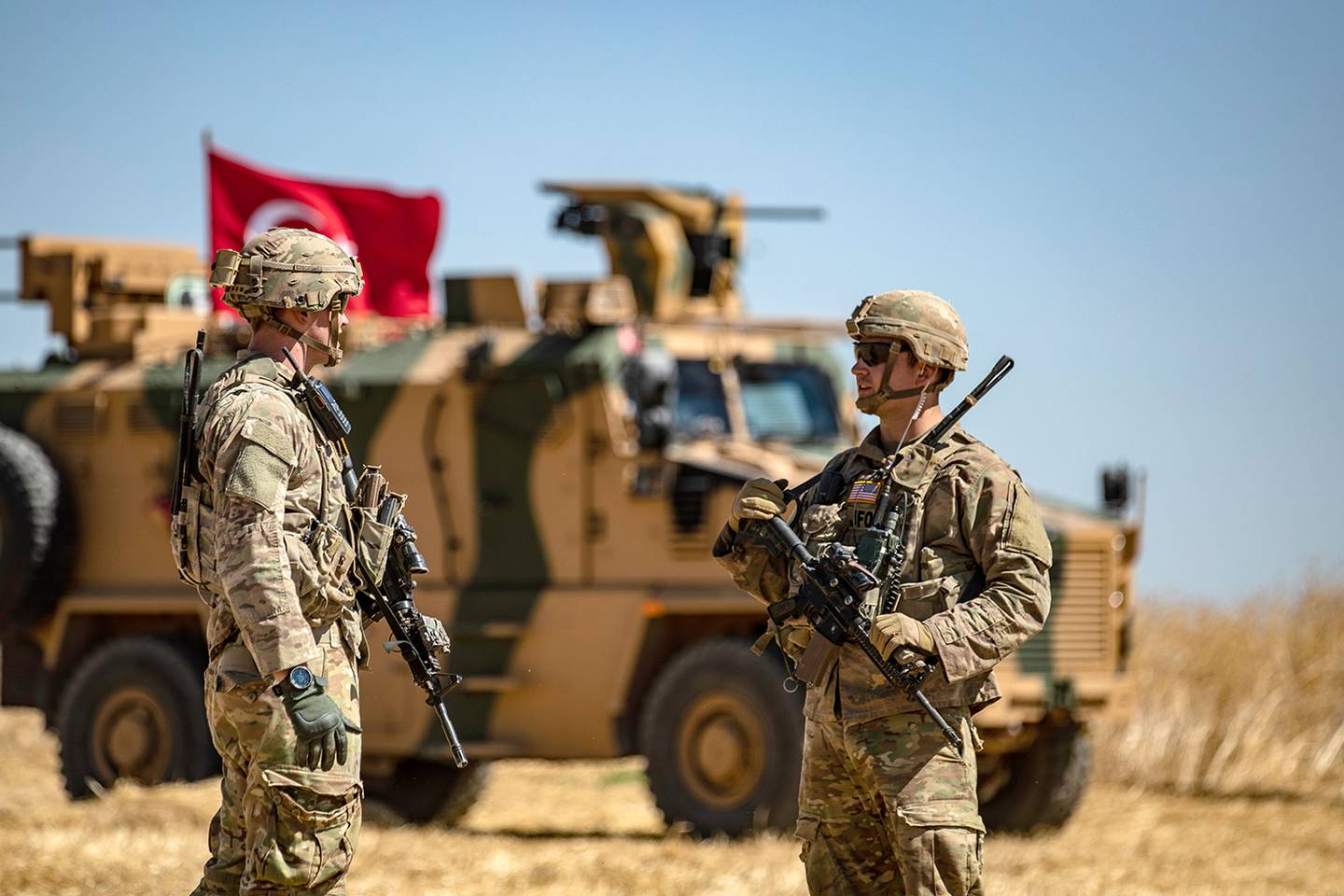 U.S. soldiers chat next to a Turkish military vehicle