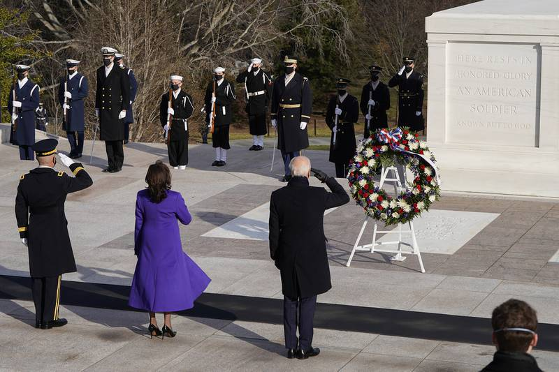 President Joe Biden, center, Vice President Kamala Harris, and Maj. Gen. Omar J. Jones salute at the Tomb of the Unknown Soldier at the Arlington National Cemetery on Jan. 20, 2021, in Arlington, Va.