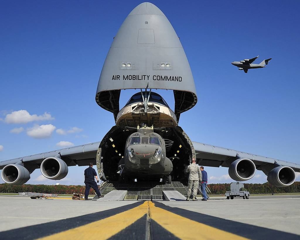 A CH-47 helicopter is unloaded from a U.S. Air Force C-5 as a C-17 takes off in the background at Westover Air Reserve Base, Mass., on Jan. 11, 2017.