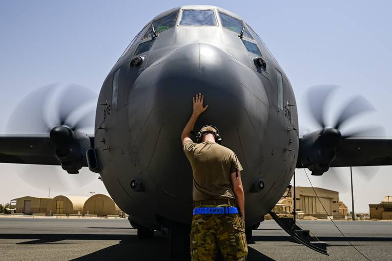 A U.S. Air Force flying crew chief assigned to the 40th Expeditionary Airlift Squadron touches the nose of a C-130J Super Hercules aircraft for good luck prior to boarding the aircraft for a mission supporting the Combined Joint Task Force - Operation Inherent Resolve, in U.S. Central Command on July 20, 2021. (Senior Airman Brennen Lege/Air Force photo)