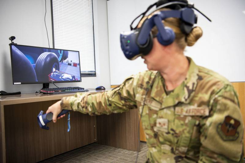 Air Force Staff Sgt. Renee Scherf, Detachment 23 curriculum engineer and MC-130H subject matter expert, demonstrates a virtual reality training system. Detachment 23's Tech Training Transformation uses tools like virtual reality training systems and artificial intelligence to transform airman education. (Staff Sgt. Keith James/Air Force)