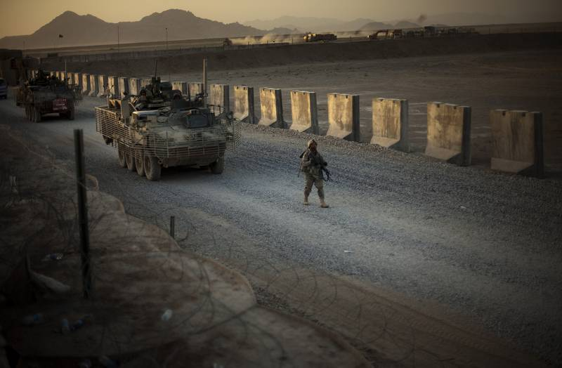 A U.S. soldier walks next to armored vehicles on a dirt road in Afghanistan.