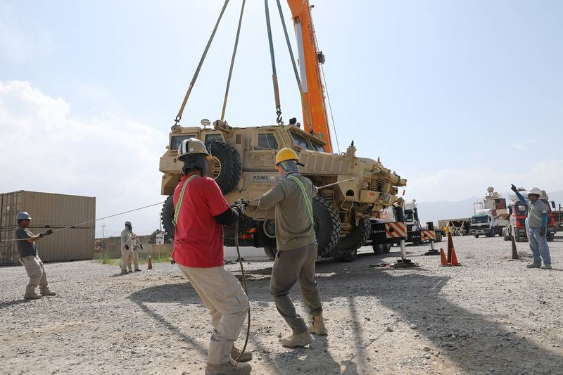 Civilian contractors prepare to load a Mine Resistant Ambush Protected vehicle on to a flatbed trailer during the retrograde cargo operation on Bagram Air Field, Afghanistan, July 12, 2020.