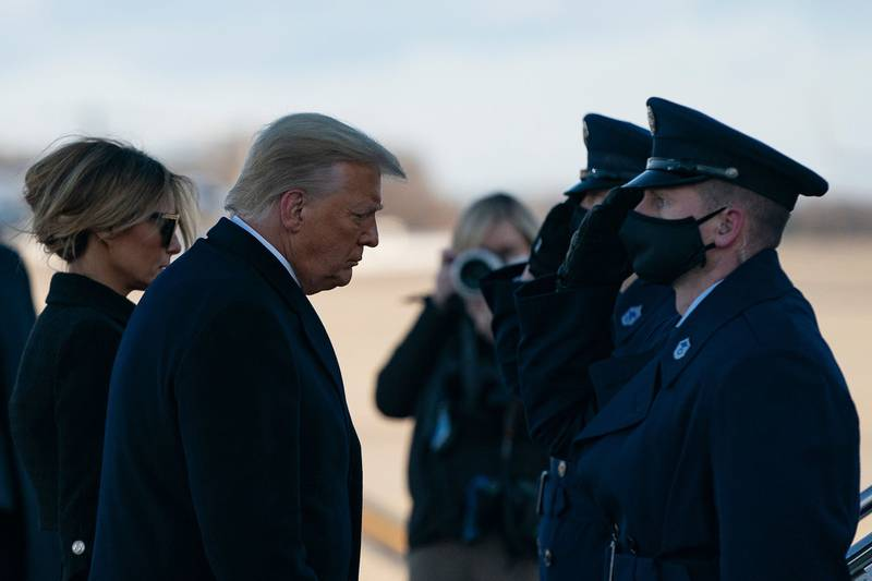 Outgoing President Donald Trump and first lady Melania Trump step out of Marine One at Joint Base Andrews in Maryland on Jan. 20, 2021.