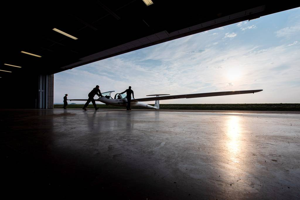 U.S. Air Force Academy cadets push a glider out of the academy's midfield hanger before taking flight in the Soaring program at Davis Airfield in Colorado Springs, Colo., on Aug. 10, 2021. (Trevor Cokley/Air Force)