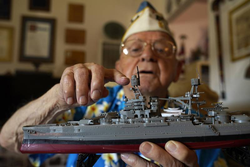 Mickey Ganitch holds up a model of the USS Pennsylvania and points to where he served as a lookout during the 1941 attack on Pearl Harbor, in the living room of his home in San Leandro, Calif., Nov. 20, 2020.