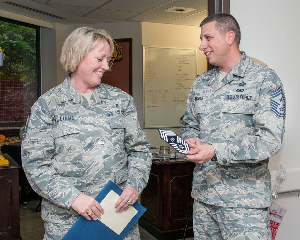 Air Force Chief Master Sgt. Steve Nichols, 60th Air Mobility Wing command chief, presents Senior Master Sgt. Lisa Williams of the 60th Medical Group with her stripe upon her selection to chief master sergeant at Travis Air Force Base, Calif., Dec. 7, 2016. (Louis Briscese/Air Force)