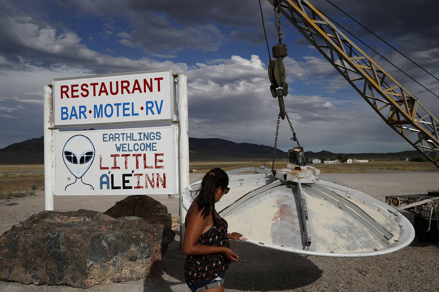 In this July 22, 2019, photo, Grace Capati looks at a UFO display outside of the Little A'Le'Inn, in Rachel, Nev., the closest town to Area 51.
