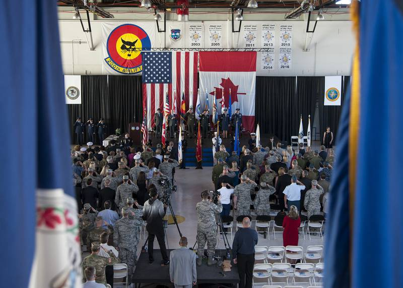 Members of both the North American Aerospace Defense Command and Northern Command, and international dignitaries from Mexico and Canada pay respects during the playing of the national anthem at the NORAD and USNORTHCOM change of command ceremony held on Peterson Air Force Base, Colo., May 24, 2018.