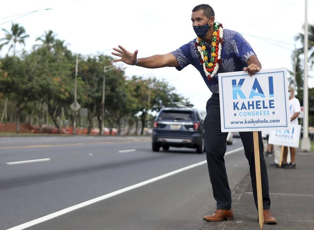 U.S. House of Representatives candidate Kai Kahele waves at people passing by while campaigning with supporters in Hilo, Hawaii, on Wednesday, Oct. 28, 2020.