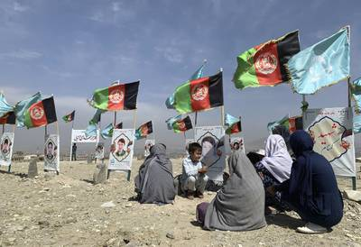 In this Sept 14, 2020, file photo, families and friends of students who were killed in local conflicts gather at the graves of their relatives, adorned with their pictures, on the outskirts of Kabul, Afghanistan.