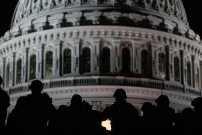 U.S. soldiers with the Virginia National Guard listen to a squad leader briefing after arriving near the Capitol in Washington on, Jan. 13, 2021.