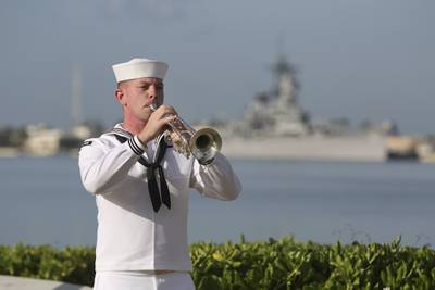 """A U.S. Navy sailor plays """"Taps"""" in front of the USS Missouri during a ceremony to mark the anniversary of the attack on Pearl Harbor, Monday, Dec. 7, 2020, in Pearl Harbor, Hawaii."""