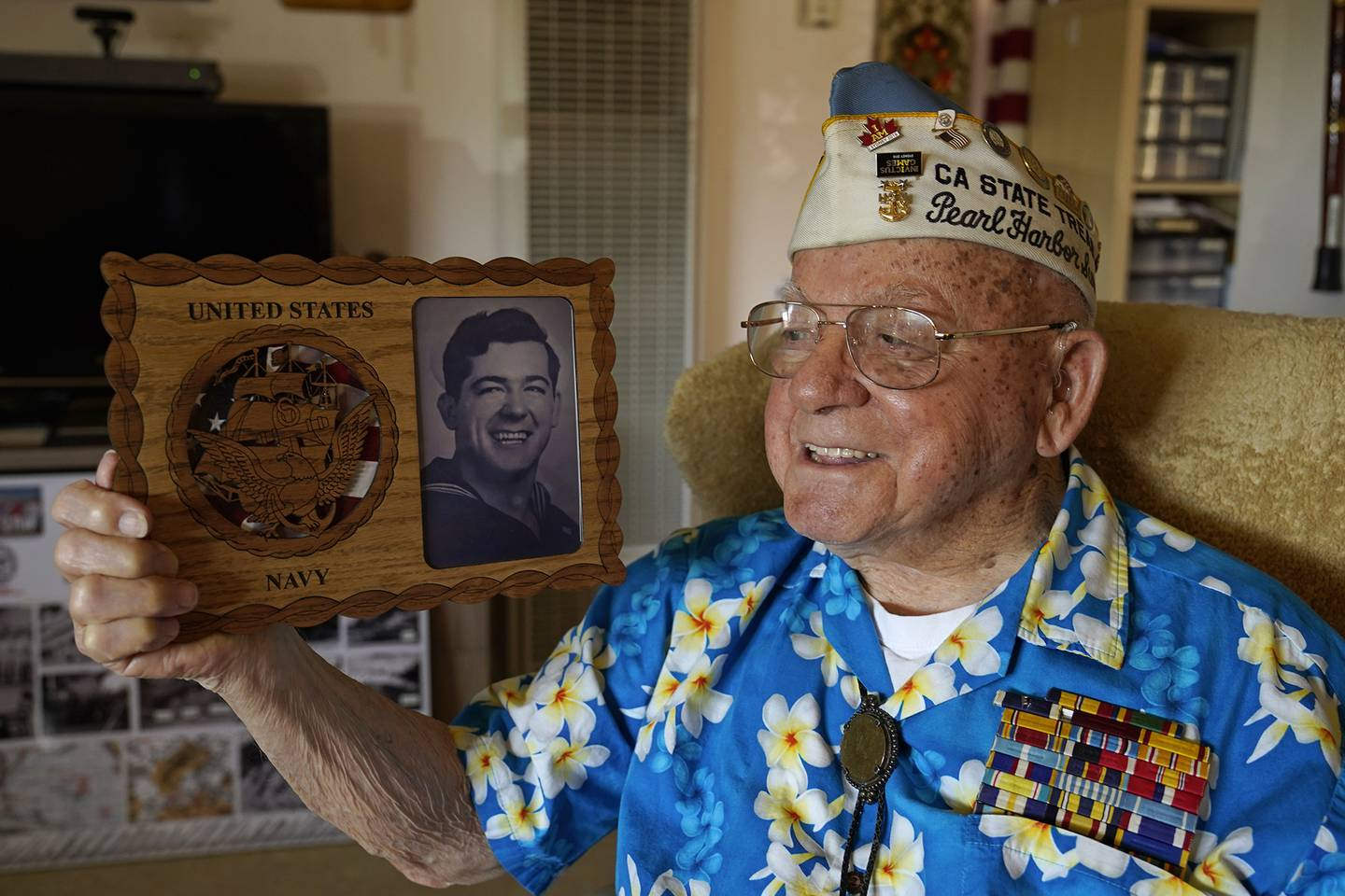 Mickey Ganitch, a survivor of the 1941 attack on Pearl Harbor, holds a plaque with a picture of himself as a young sailor, while sitting in the living room of his home in San Leandro, Calif. Nov. 20, 2020.